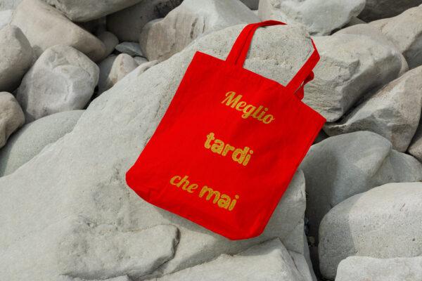 Czerwona torba z włoskim cytatem meglio tardi che mai